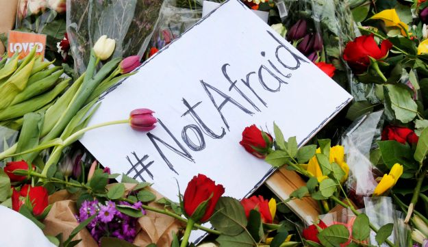 A sign is placed among flowers near the cultural center where Finn Nørgaard was shot and killed