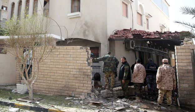 Libyan security forces inspect the site of a bomb explosion
