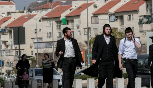 Pogrow lives in Beit Shemesh, near Jerusalem. Below, three ultra-orthodox men walk in Ramat Beit Shemesh.