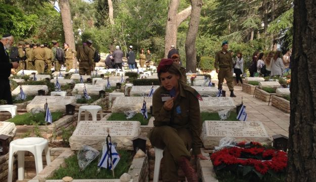 A soldier prays beside a grave at the national cemetery on Mount Herzl, Jerusalem, on Memorial Day,