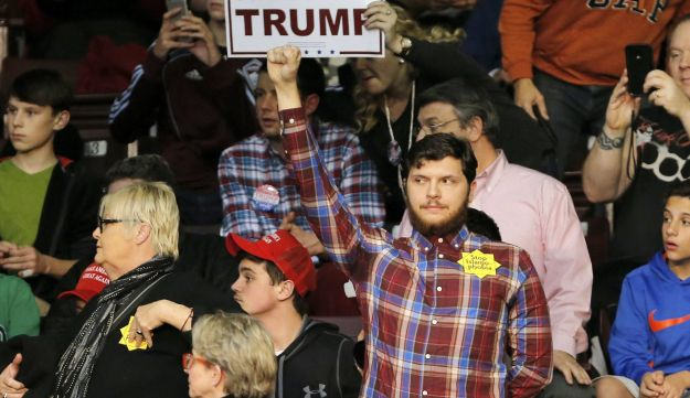 A protester wearing a yellow star stands as republican presidential candidate Donald Trump speaks during a campaign event in Rock Hill, South Carolina January 8, 2016.