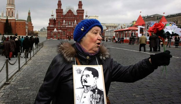 A Communist supporter wears a portrait of Josef Stalin as she and other Communists and supporters line up to put flowers on Stalin grave outside the Kremlin wall, to mark 57 anniversary of his death in Moscow, Friday, March 5, 2010.