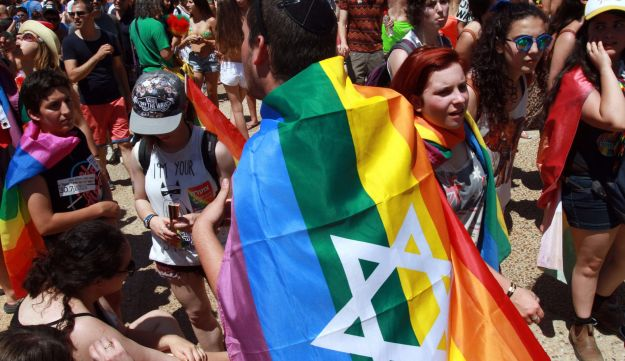 An Israeli with a rainbow-colored flag draped around his shoulders attends the annual gay pride