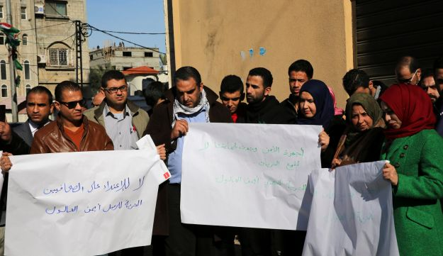 Palestinian journalists hold placards during a protest calling for the release of journalist Ayman al-Aloul, Gaza City, January 5, 2016.