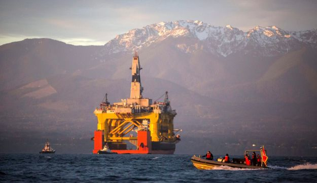 In this April 17, 2015 file photo, with the Olympic Mountains in the background, a small boat crosses in front of an oil drilling rig as it arrives in Port Angeles, Wash. aboard a transport ship after traveling across the Pacific. Royal Dutch Shell hopes to use the rig for exploratory drilling.