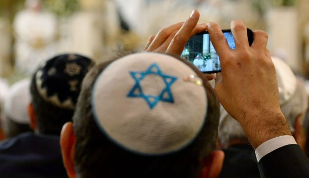 A member of the Rome's Jewish community takes pictures of Pope Francis during his visit in Rome's main Synagogue, on January 17, 2016.