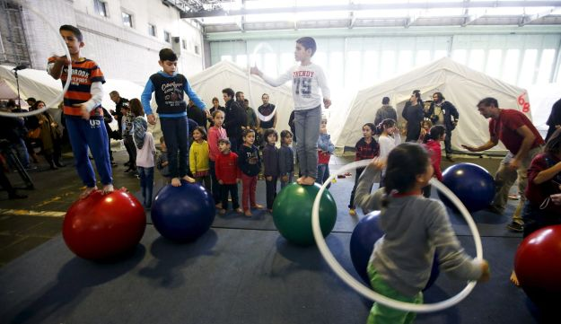 Migrant children play with equipment provided at a shelter for migrants inside a hangar of the former Tempelhof airport, Berlin, Germany, December 9, 2015.