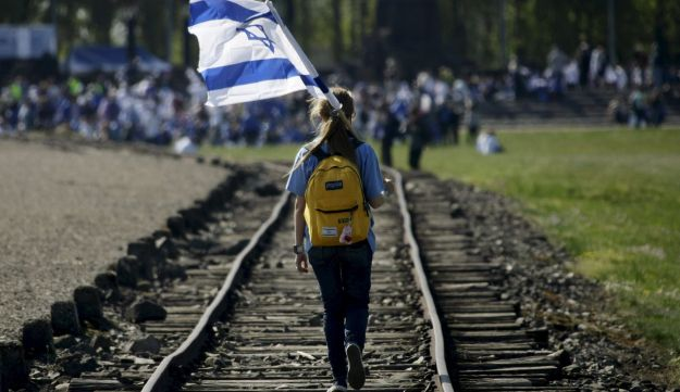 A girl holding an Israeli flag walks through the former Nazi death camp of Birkenau (Auschwitz II) in Oswiecim, southern Poland.
