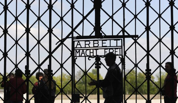"Visitors walk past a gate with ""Work makes Free"" written on it at the memorial site of the former Nazi concentration camp in Dachau, southern Germany on April 24, 2009."