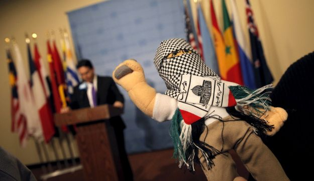 "Israel's UN Ambassador Danny Danon holds a doll he said was part of a shipment recently stopped of ""thousands of dolls dressed as terrorists."" United Nations Security Council meeting. January 26, 2016."