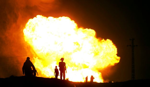 Bedouins watch as flames rise after gunmen blew up a terminal of the natural gas pipeline in Sinai.