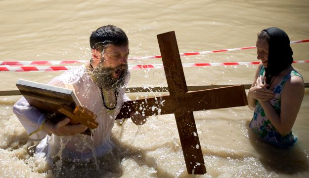 Orthodox Christians immerse themselves in the Jordan River at a baptism ceremony.