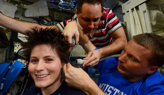Samantha Cristoforetti getting her hair cut by NASA astronaut Terry Virts during the mission in outer space. The hair bits are being vacuumed up by Russian cosmonaut Anton Shkaplerov because otherwise the astronauts would have spent the rest of the mission breathing in hair bits.