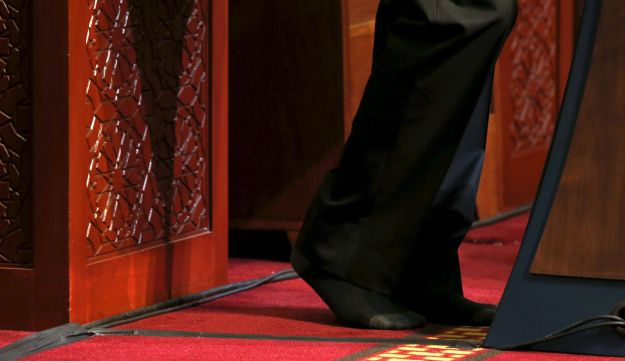 U.S. President Barack Obama goes without shoes, out of deference, as he delivers remarks at the Islamic Society of Baltimore mosque in Catonsville, Maryland February 3, 2016.