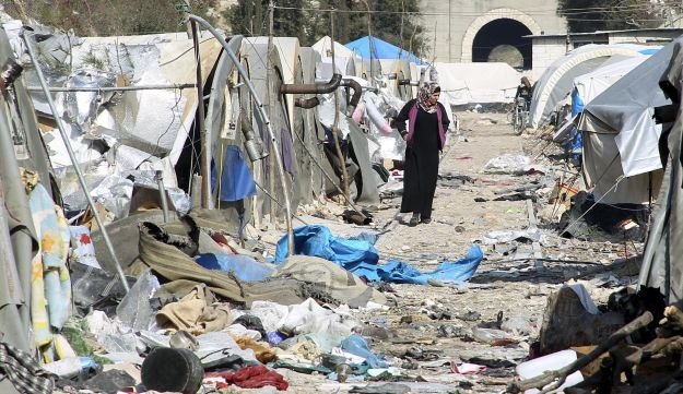 A woman inspects damage at a camp for IDPs after it was hit by what residents said was shelling carried out by Assad forces near the Syria-Turkey border, Jan. 31, 2016.