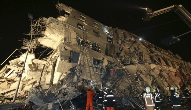 Rescue personnel work at a damaged building after an earthquake in Tainan, southern Taiwan, February 6, 2016.