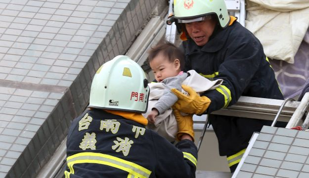 Rescue workers remove a baby from the site where a 17-storey apartment building collapsed after an earthquake hit Tainan, February 6, 2016.