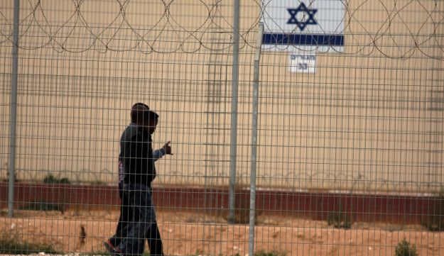 File photo: Two asylum seekers walk past a fence at the Holot detention facility in the Negev.