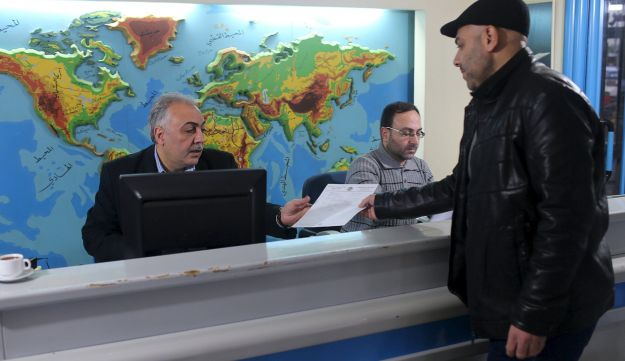 Palestinian travel agent Nabil Shurafa receives a document from a client at his office in Gaza City, Feb. 4, 2016.
