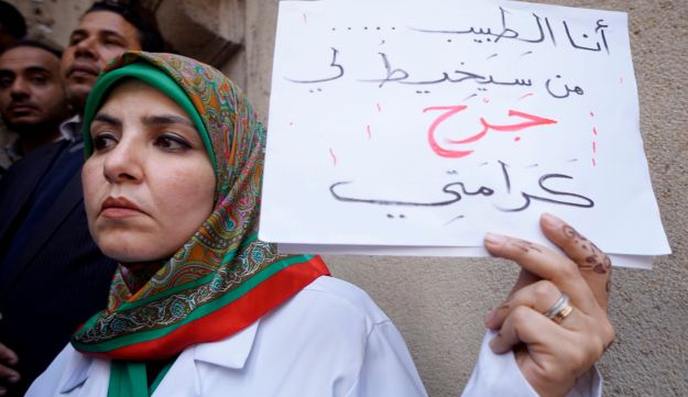 "An Egyptian doctor holds a sign reading, ""I'm the doctor, who will treat my dignity wound?"" during a protest against police abuses, Cairo, February 12, 2016."
