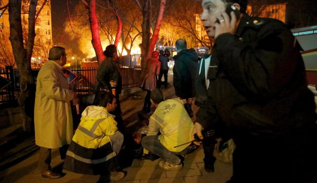 Emergency workers help an injured person on the ground near the explosion site in Ankara, Turkey, February 17, 2016.