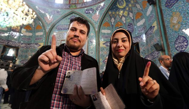 Iranians display their ink-stained finger after casting their ballot for both parliamentary elections and the Assembly of Experts at a polling station in Tehran on February 26, 2016.