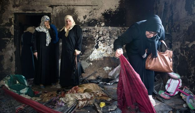 Palestinian women look at the damage at the Dawabsheh family's home in the West Bank village of Duma, August 4, 2015.