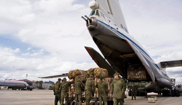 Russian air force personnel load cargo on board a Syrian Il-76 plane at the Hemeimeem air base in Syria, January 20, 2016.