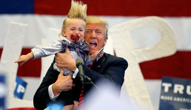 Trump holds up a child he pulled from the crowd as he arrives to speak at a campaign rally in New Orleans, March 4, 2016.