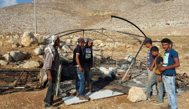 Palestinians looking over the charred remains of the tent.
