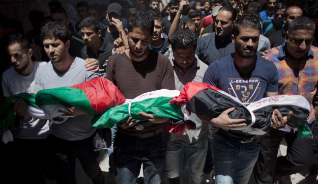 Palestinian mourners carry the bodies of three children who were killed in a fire caused by a candle in Gaza City, May 7, 2016.