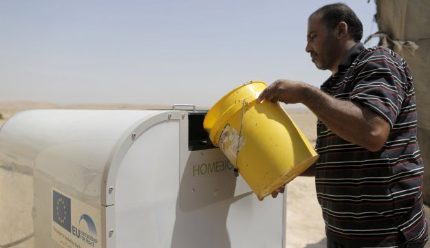 Nayef Zayed empties a bucket of waste into a HomeBioGas portable reactor.
