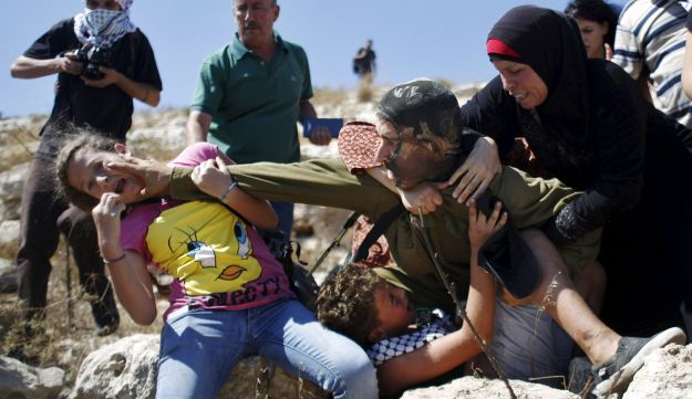 Palestinians scuffle with an Israeli soldier in Nabi Saleh.