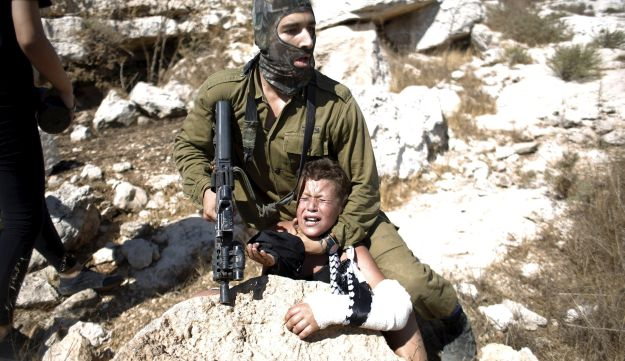 An Israeli soldier detains a Palestinian boy