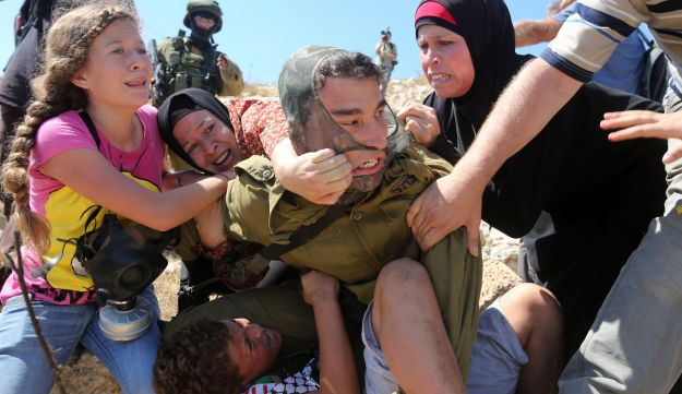 Palestinians fight to free a Palestinian boy held by an Israeli soldier during clashes on August 28