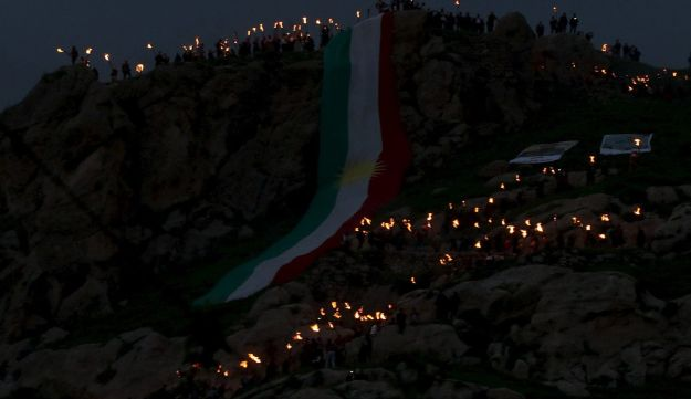 Kurdish people carry fire torches up a mountain where a giant flag of the autonomous Kurdistan region is laid in the town of Akra, Iraq, March 20, 2016.