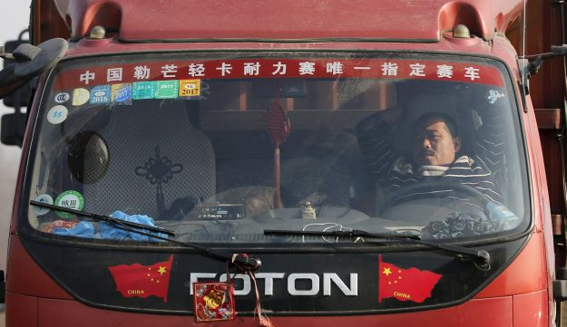 A driver asleep in his truck in a traffic jam on a highway near Beijing.