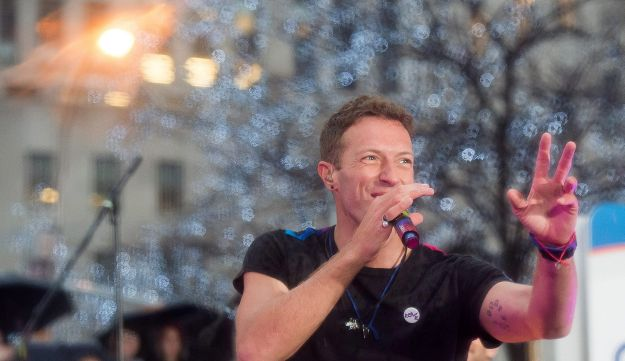 "Chris Martin from the band Coldplay performs in the rain on NBC's ""Today"" show at New York's Rockefeller Plaza on March 14, 2016."