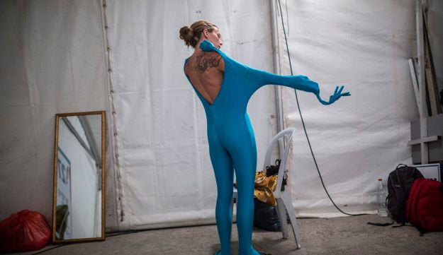 A woman wears her full solid-coloured bodysuit before taking part in a street art performance