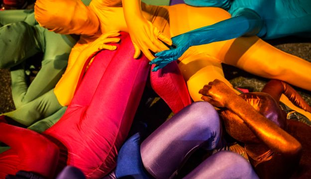A group of people wearing full solid-coloured bodysuits take part in a street art performance