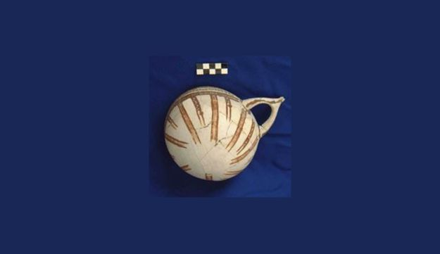 Early white Slip II bowl, typical of Cypriot pottery but found in the Tell el- Ajjul excavation in Gaza. The pot has brown striped decorations and a pointed handle.