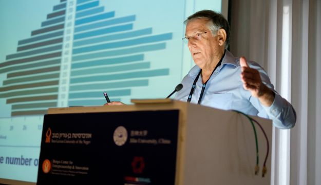 Prof. Dan Shechtman addressing the Third Global Entrepreneurship and Innovation Conference, hosted by Ben Gurion University of the Negev, May 16, 2016. Behind the professor is a graphic demonstrating the unique demographics of China - a breakdown of the population by age group.