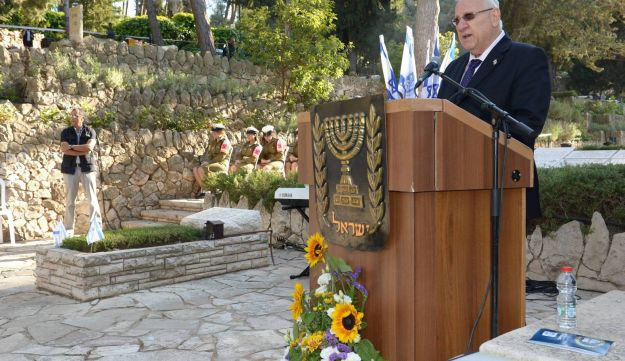 President Reuven Rivlin speaking at a memorial to David Raziel, Har Herzl, Jerusalem, May 4, 2015. Rivlin is wearing a dark blue suit and tie and stands at a dais bearing the emblem of the State of Israel.