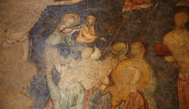 """A scene in the Church of the Resurrection, Abu Ghosh, Israel, showing Christ on the crucifix; an angel with her back to the Crucifixion, a female figure labeled """"Synagoga"""" beneath whom are soldiers - and, with a white turban on his head, the Witnessing Centurion."""
