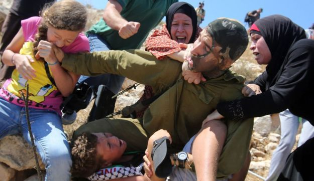 Palestinian women trying to free the teen, at Nabi Saleh protest.