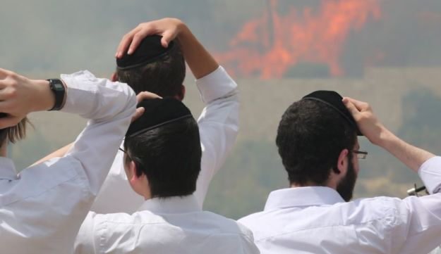 People watch a fire blazing in the Ramot forest on the outskirts of Jerusalem on Thursday, May 26, 2016.