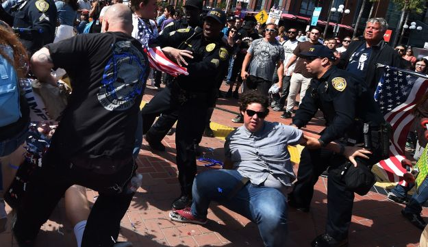 Protesters and supporters of Republican U.S. presidential candidate Donald Trump fight during a rally outside Trump's event in San Diego, California, May 27, 2016.