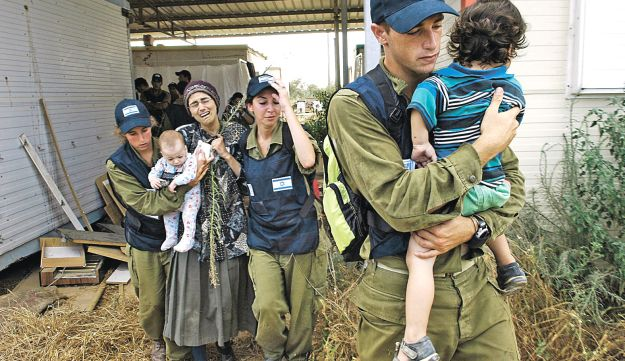 Soldiers lead out an Israeli family from their home in Kfar Dorom in Gaza during the disengagement, August 18, 2005.