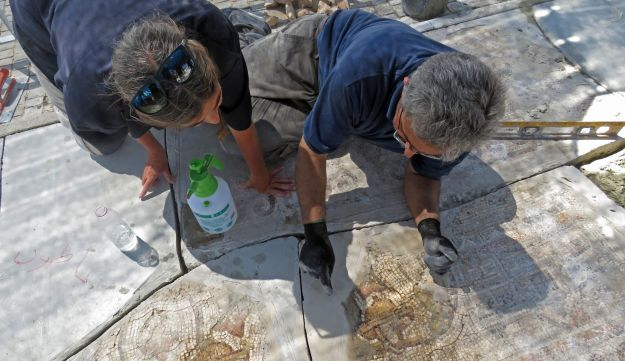 IAA workers conserving the mosaic.