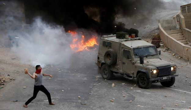 Palestinian youths throw rocks at Israeli military vehicle in Nablus, Oct. 6, 2015.